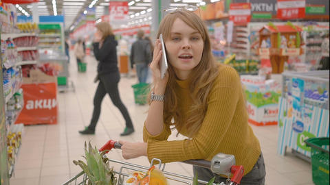 Young cheerful woman in supermarket with shopping trolley talking by phone ビデオ