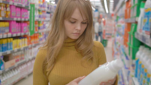 Young woman choosing household chemicals in supermarket Footage