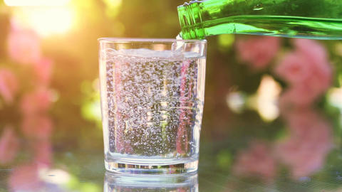 Green bottle with mineral water on blurred bokeh background Footage