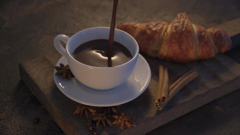 Pouring hot chocolate with croissants and cinnamon sticks on grunge table Footage