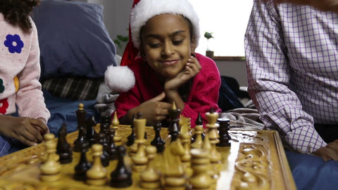 Smiling girl in santa hat watching chess game Image