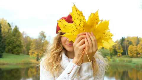 Attractive Caucasian woman posing with maple leaves in autumn Park Footage