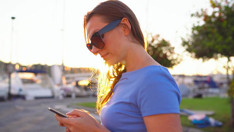 Woman in sunglasses using smartphone while walking down a dock with a lot of Footage