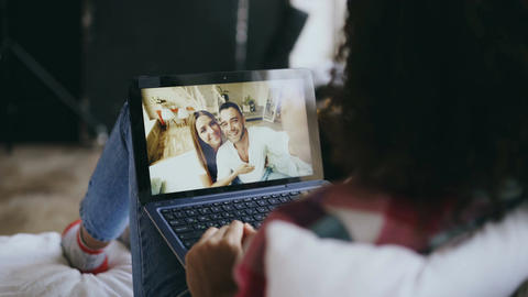 Curly young woman having video chat with friends using laptop camera while lying Footage