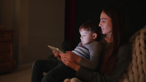 Beautiful woman mother sitting in a chair his home with son on his lap watching Footage
