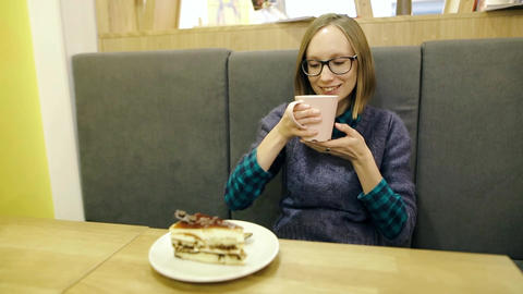 Dreamy young girl in glasses drinking hot scandinavian tea with blueberries and Footage