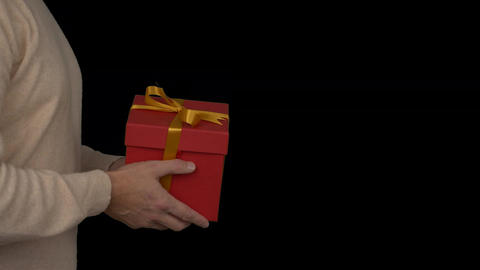 Red gift box in hands of adult caucasian man in beige sweater. Close up locked Footage