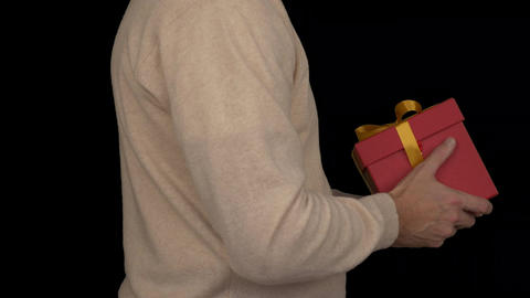 Caucasian man in beige sweater is holding a gift box in hands. Side view of man Footage