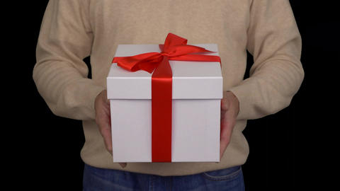 Caucasian man in beige sweater is holding a white gift box in hands. White gift Footage
