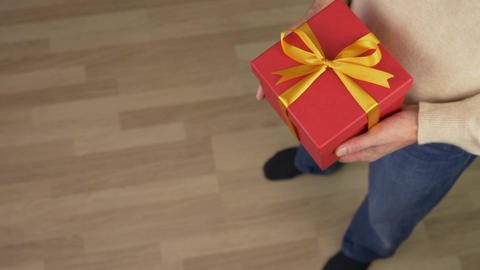 Caucasian man in beige sweater is holding a gift box in hands. Top view of man Footage