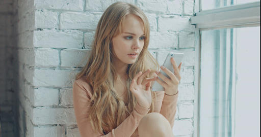 Young attractive woman using mobile phone while sitting near the window at home Footage