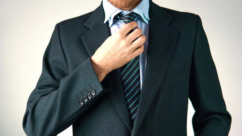 A stylish man dresses a suit, straightens a tie and jacket. looks elegant Footage