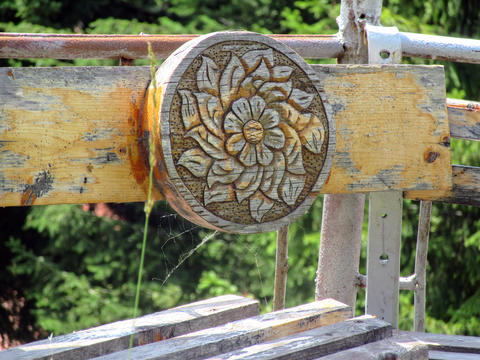 Wood carving on a bench in a mountain village, Bulgaria. With a spider web Fotografía