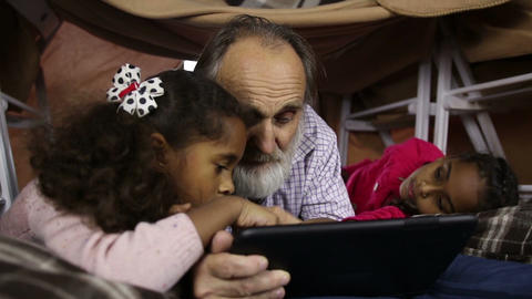 Kids teaching grandpa to use smart gadget Live Action