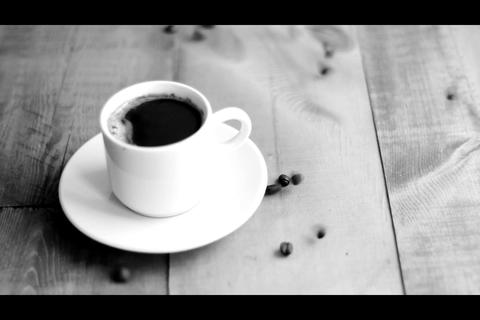 Cup of coffee beside falling coffee beans on wooden board. Black and white Footage