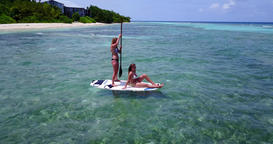 v08328 2 pretty young girls on a surfboard paddleboard with aerial view in warm Footage