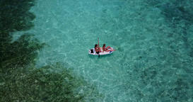 v08268 2 pretty young girls on a surfboard paddleboard with aerial view in warm Footage