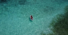 v08266 2 pretty young girls on a surfboard paddleboard with aerial view in warm Footage