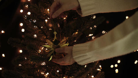 Female decorate Christmas tree with gold star decoration on bokeh lights Live Action