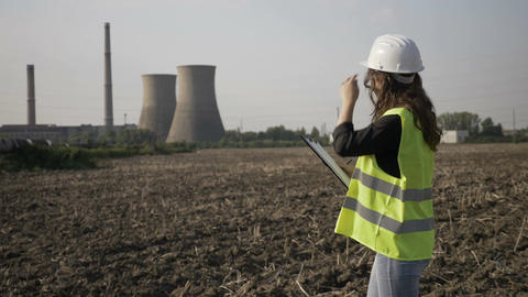 Beautiful young female technician specialist examining power plant area and Footage