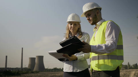 Engineer woman and young foreman analyzing industrial field plans and completing Live Action