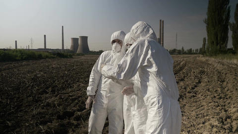 Biologists workers in hazmat clothing looking at contaminated piece of soil Footage