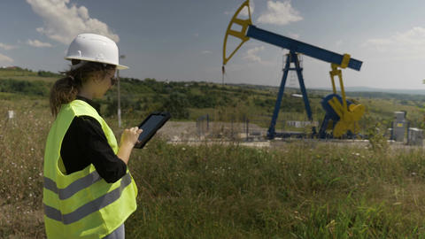 Supervisor engineer woman using a tablet pc inspecting extracting oil pump unit Footage