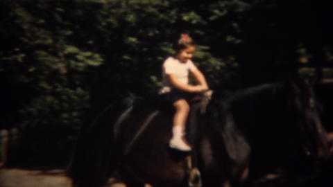 1937: Young girl 1st time riding horse helped by proud trainer and father Footage