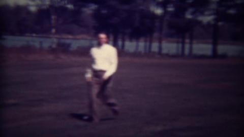 1937: Country club golfers walking fairway with caddies carrying golf clubs Live Action