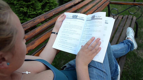 Woman lying down on a bench and read a book Footage