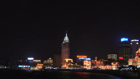 The Bund at Night with the Huang Pu River and a Sightseeing Boat(Pan to the Left Footage