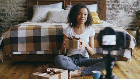 Young cheerful african american girl recording video blog about packing Live Action