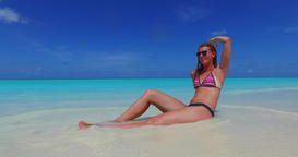 v09990 beautiful young girl in bikini sunbathing and relaxing by the aqua blue Live Action