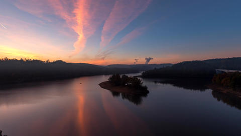 Time lapse footage of colourful rich sunrise over a lake with small island in a Live Action
