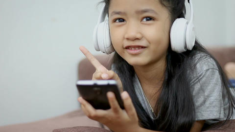 Asian little girl listen to the music by white wireless headphone with happiness Footage