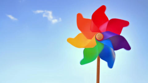 Colorful pinwheel toy against blue sky and clouds ビデオ