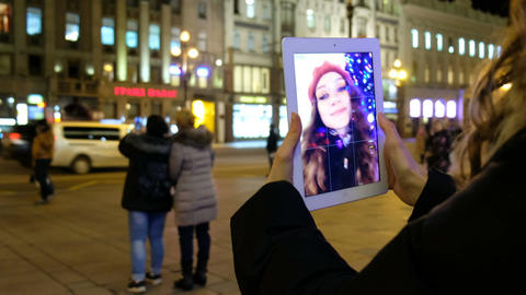 Attractive young girl taking pictures of herself on the screen in the background Footage
