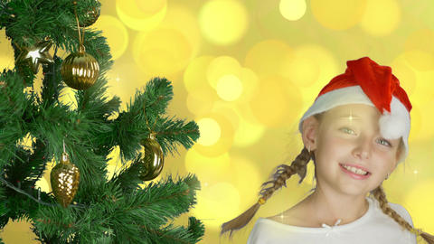 Happy young girl dancing near christmas tree in Santa red hat. Happy young Footage