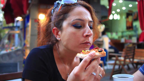 Portrait of young woman eating a slice of pizza ビデオ