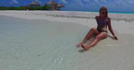 v09981 beautiful young girl in bikini sunbathing and relaxing by the aqua blue Live Action