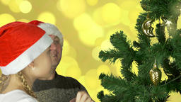 Young caucasian girl in red Santa hat decorate green christmas tree with golden Footage