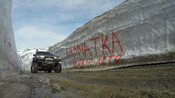 Off-road expedition car driving on mountain road in snow tunnel surrounded by Archivo