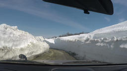 Automobile driving on mountain road in snow tunnel surrounded by high snowdrifts Footage