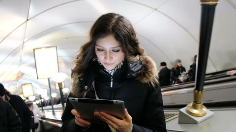 Young attractive Caucasian girl looking at the screen of the tablet and holds it ビデオ