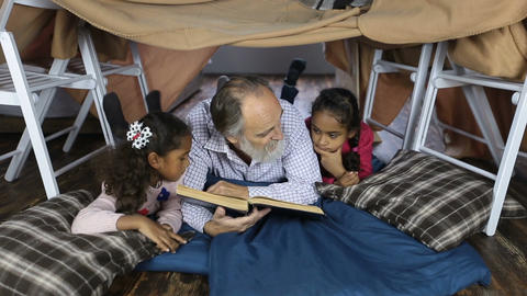 Old man reading the Bible with grandchildren Footage