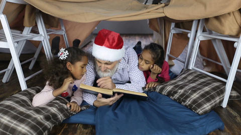 Grandpa in santa hat reading a book with kids Archivo