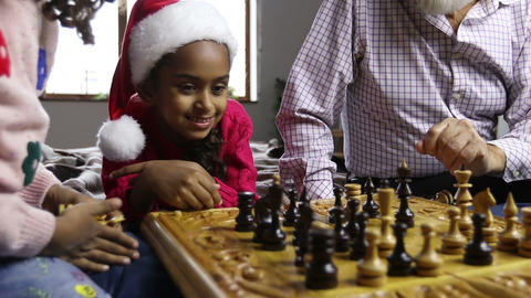 Cute little girl in santa hat watching chess game Image