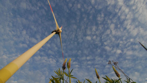 The blades of the wind station are spinning against the beautiful blue sky Footage
