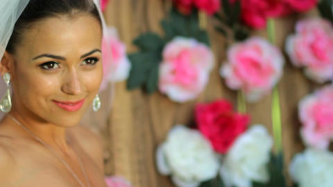 Beautiful bride against the background of a wooden wall with peonies Live Action