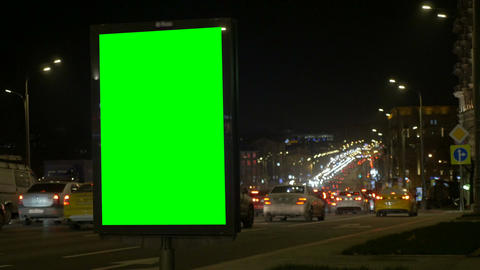 A Billboard with a Green Screen on a Busy Street. Blurred background of lights Live Action